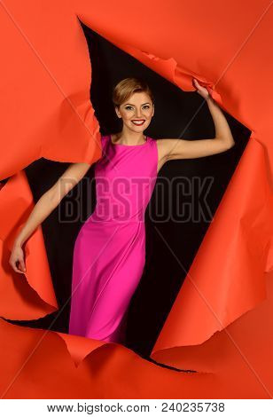 Pretty Blonde Girl In Pink Dress With Glamour Makeup, Red Lips Comes Out Through Gap In Red Paper. A