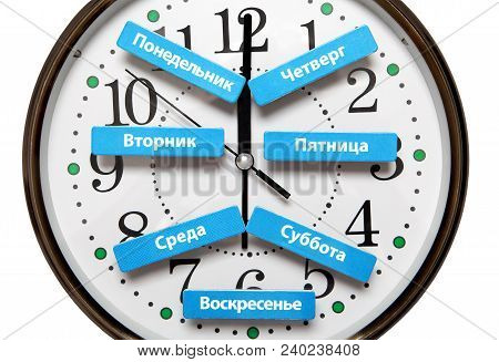 The Names Of The Days Of The Week In Russian Lie On The Background Of The Clock Face.