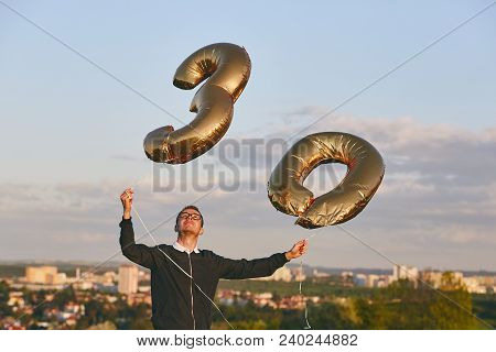 Man Celebrates Thirty Years Birthday. Person Holding Helium Balloons In Shape Of Number 30 Against C