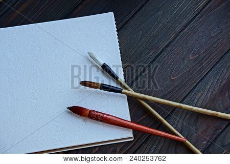 Three Tassels On A White Sheet Of Notepad On A Wooden Table