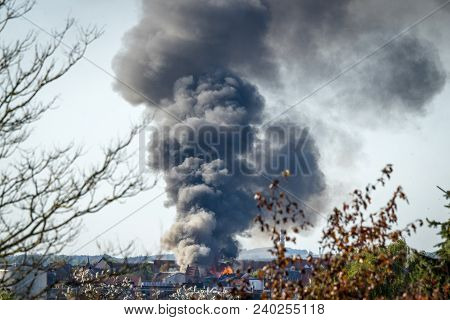 House On Fire In A City With Black Smoke Covering The Sky In The Daytime