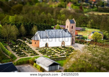 Danish Church With A Cemetary In A Small Village Surrounded By Trees Seen From Above