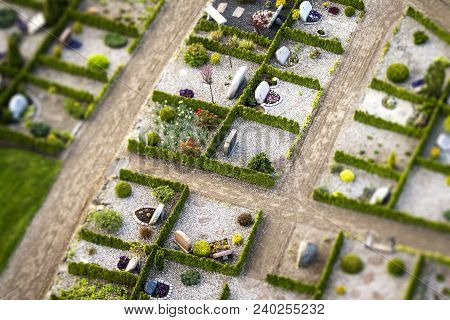 Cemetery With Green Hedges And Gravestones Decorated With Flowers On A Sunny Day Seen From Above