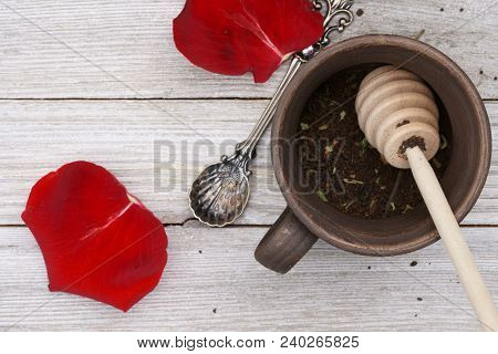 Top Down View Of Tea Leaves In A Tea Cup Made Of Clay With A Red Rose Petals.