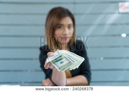 Businessman Giving Money. She Wears A Black Suit. And Have A Bright Look. American Dollars.