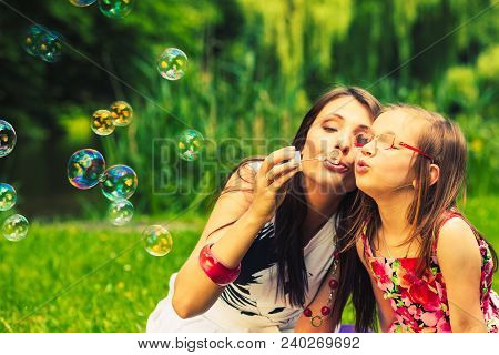 Mother And Daughter Child Blowing Soap Bubbles Outdoor. Parent And Kid Having Fun In Park. Happy And
