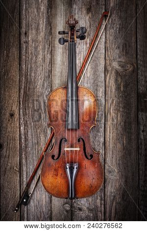 Classical Used Violin With Bow On Old Wooden Background