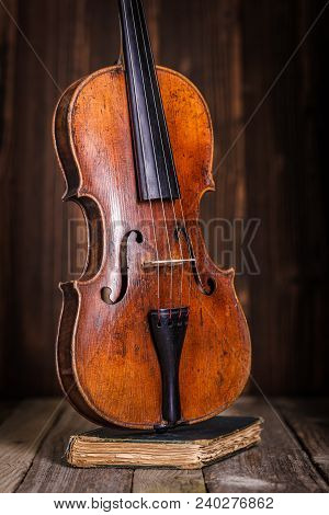 Front View Of A Classical Old Violin On Wooden Background