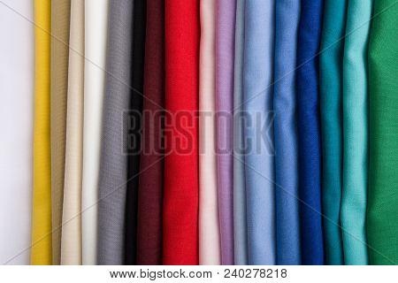 A Pile Of Multicolored Fabrics. Rainbow Fabric Background. Pile Of Bright Folded Fabric
