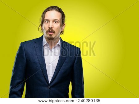 Handsome young man scared in shock, expressing panic and fear