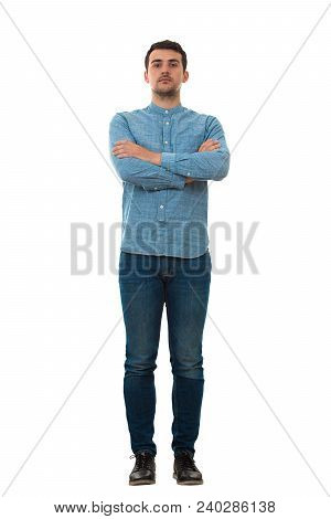 Full Length Portrait Of A Serious Young Man With Crossed Hands Isolated On White Background. Confide