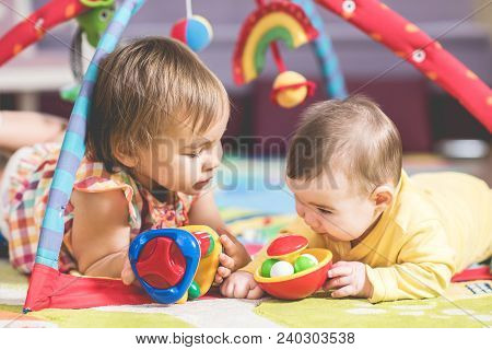 Little Girl And Her Baby Brother Are Playing With Toys Together At Home