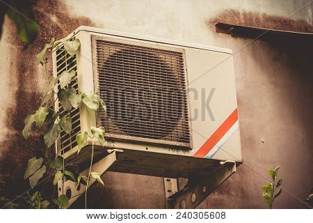 Old Rusting Metal Exterior Fitted Air Conditioning Unit Located Outside Of Building Needing Maintena