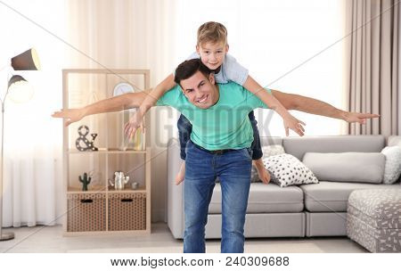 Young man playing with little boy indoors. Child adoption