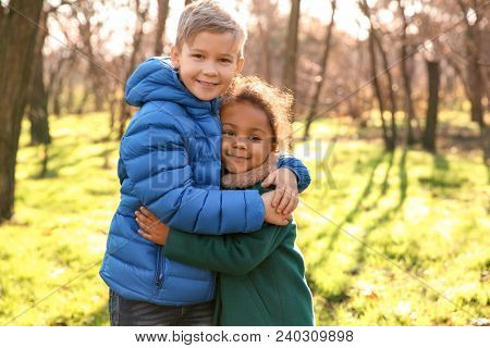 Cute boy and African-American girl outdoors on sunny day. Child adoption