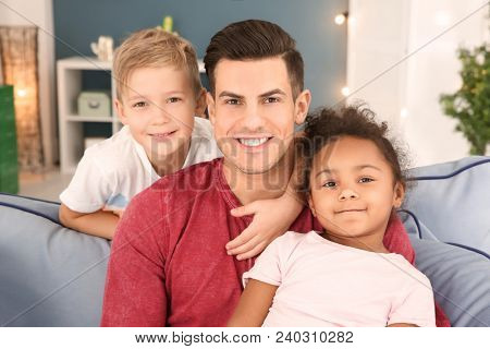 Young man and little kids indoors. Child adoption