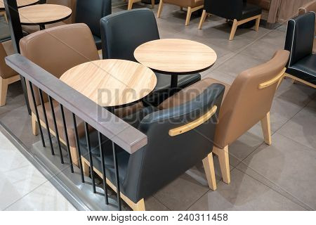 Dining Wooden Table With Black And Brown Leather Chairs For Dining Out On Ceramic Tile Floor.