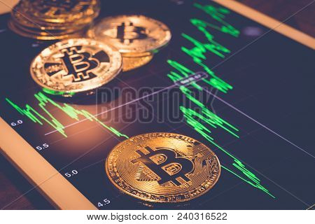 Cryptocurrency Gold Metal, Focus On Bitcoin Sign, Coins Put On Tablet Screen That Showing Green Pric