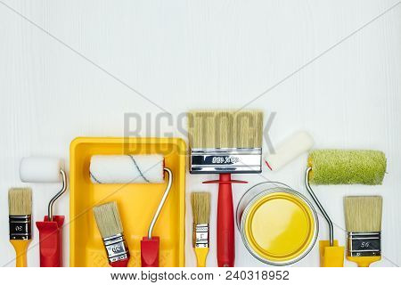 Various Paint Brushes, Rollers, Paint Cans And Paint Tray On White Wooden Background. Flat View