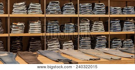 Jeans Pants On The Store Shelf. Blue Jeans Denim Collection Jeans Stacked. Jeans Hanging On The Vest