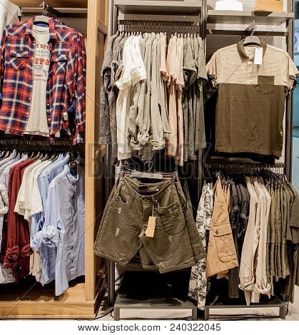 Shorts, Shirts, T-shirts And Jacket On The Store Shelf. Fashionable Clothes On The Shelves In The St