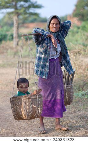 Myinkaba, Myanmar - January 8, 2011: Burmese Woman Carrying Baby And Firewood In Basket Over Fields