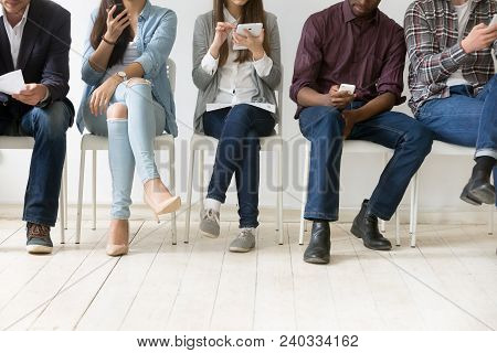 Diverse Black And White People Sitting In Row Using Smartphones Tablets, Multiracial Men And Women W