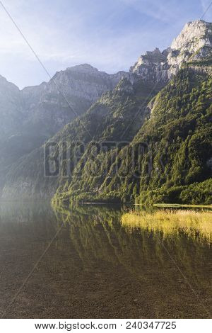 Sunny  foggy morning in the Swiss Alps. Mountain lake Klontalersee in haze on  background of majestic mountains.  Glarus canton. Switzerland. poster