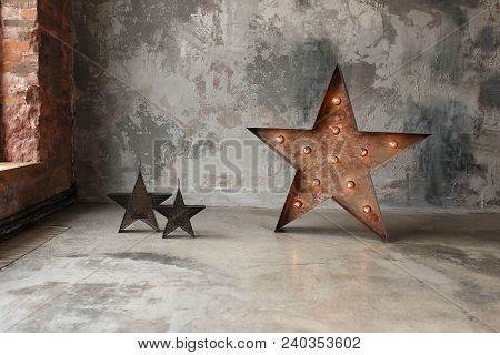 Decorative Star With Lamps On A Background Of Concrete Wall. Modern Grungy Loft Interior.