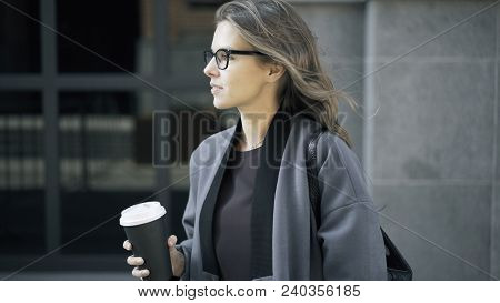 Woman Wearing Glasses And A Gray Coat Is Holding A Cup Of Coffee And Smilng. A Downtown Background.