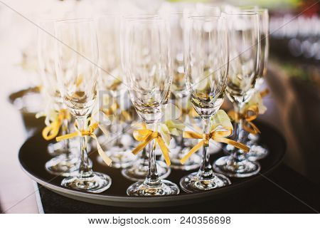 A Set Of Tall Wine Glasses Decoration With Gold Ribbon On The Tray With Selected Focus On One Wine G
