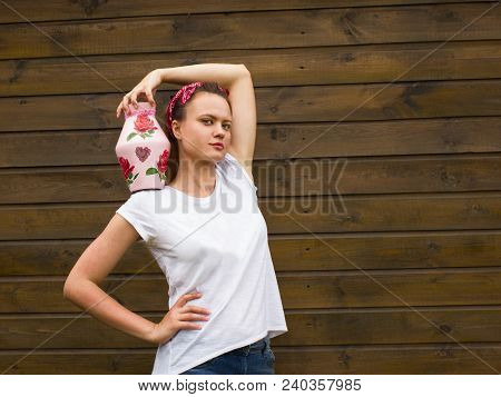 Attractive  Serious Young Woman With White T-shirt On The Wooden Background, Holding Decorative Jug