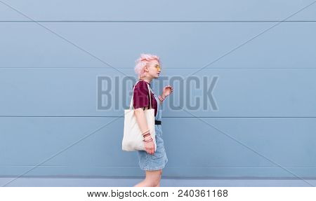 Stylish Girl Walking Around The Blue Wall With A Shopping Bag. Girl With Pink Hair, Glasses And Shop