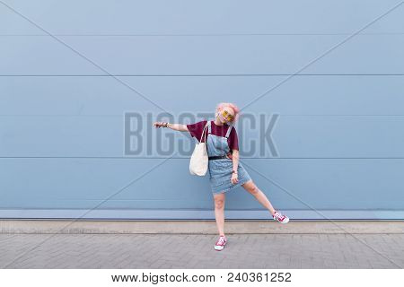Positive Stylish Girl In Glasses And Jeans Wearing A Shopper In Her Hands Against The Background Of