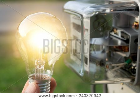 Close-up Hand Of Person Holding Light Bulb From Outdoor With Watt Hour Meter Beside