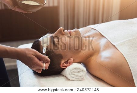 Man Getting Facial Nourishing Mask By Beautician At Spa Salon, Closeup. Apply Face Mask, Spa Beauty