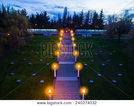 Drone View Of Stairs, Lawn And Square With Eternal Flame Of Illuminated Zavokzalnyy Memorial Complex
