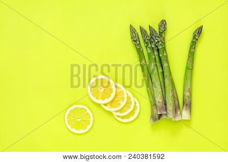 Beautiful Food Art Background. Asparagus Sprouts And Sliced Lemon On Bright Green Surface.