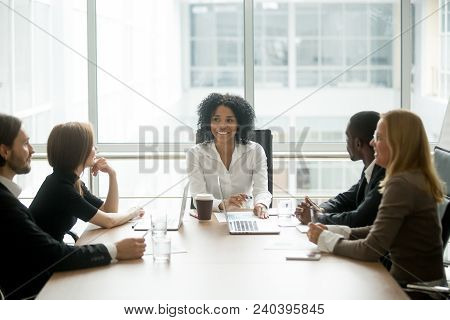 Smiling Friendly African Female Boss Leading Corporate Diverse Team Meeting Talking To Multiracial P