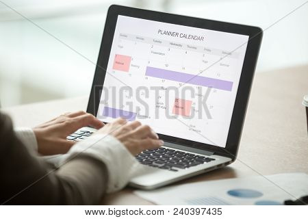 Businesswoman Planning Day Using Digital Planner Or Calendar Software Application On Laptop Screen,