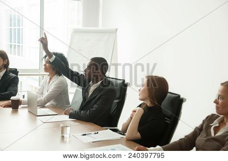 African Businessman In Suit Raising Hand At Corporate Diverse Group Meeting, Black Employee Voting A