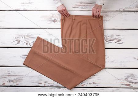 Hands And Trousers On Wooden Background. Young Women Hands And Classic Trousers On Wooden Table. Sto