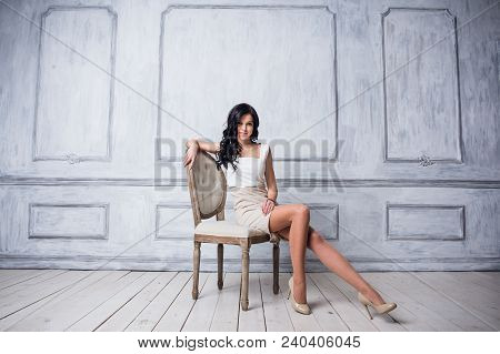 Portrait Of Attractive Young Woman Sitting In A Chair. Elegant White Dress. White Floor And White Wa