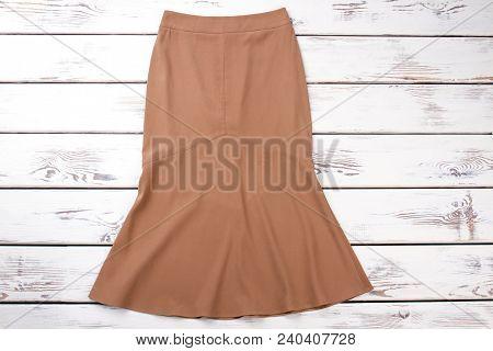 Female Beige Skirt, Top View. Women Classy Skirt On White Wooden Background. Brand Apparel On Sale.