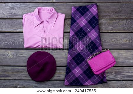 Set of female elegant attire. Women purple color shirt and skirt, wooden background. Feminine fashion clutch and beret. Ladies classy apparel flat lay. poster