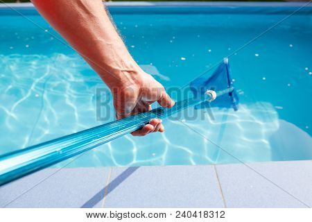 Worker Make Maintenance Of Swimming Pool. Male Hand Hold Pool Net Cleaner. Focus On The Hand.