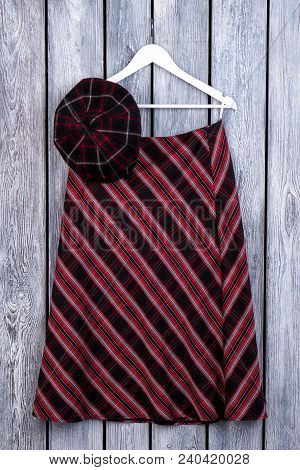 Women Casual Apparel On Wooden Background. Female Red And Black Skirt Hanging On Hanger. Feminine Fa