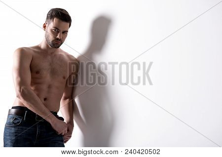 Manliness Beauty Concept. Portrait Of Charming Sexual Shirtless Bristled Guy Is Leaning On Wall Whil