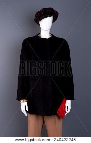 Female Mannequin In Cap And Overcoat. Dummy Dressed In Black Female Coat, Grey Background. Feminine