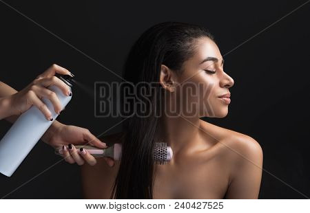 Profile of calm lady making hairdo. Hairdresser using hairspray and comb. Isolated on background poster